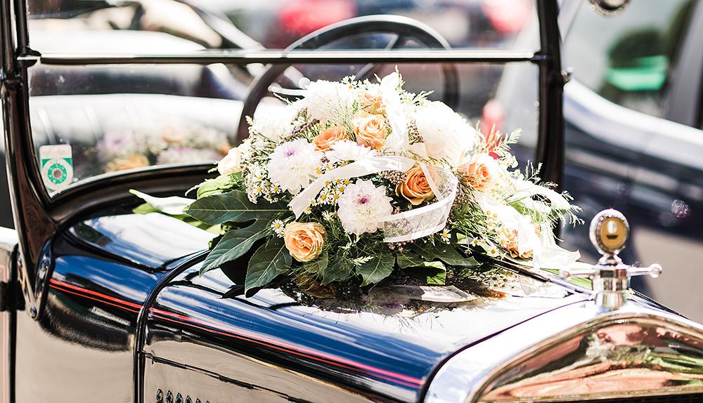 Stilpunkte: Zur Hochzeit im klassischen Oldtimer-Cabrio mit Blumenschmuck auf der Motorhaube